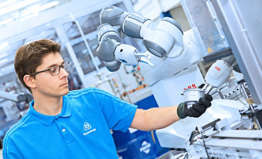 thyssenkrupp employee with collaborative robot Yumii in a steering production plant