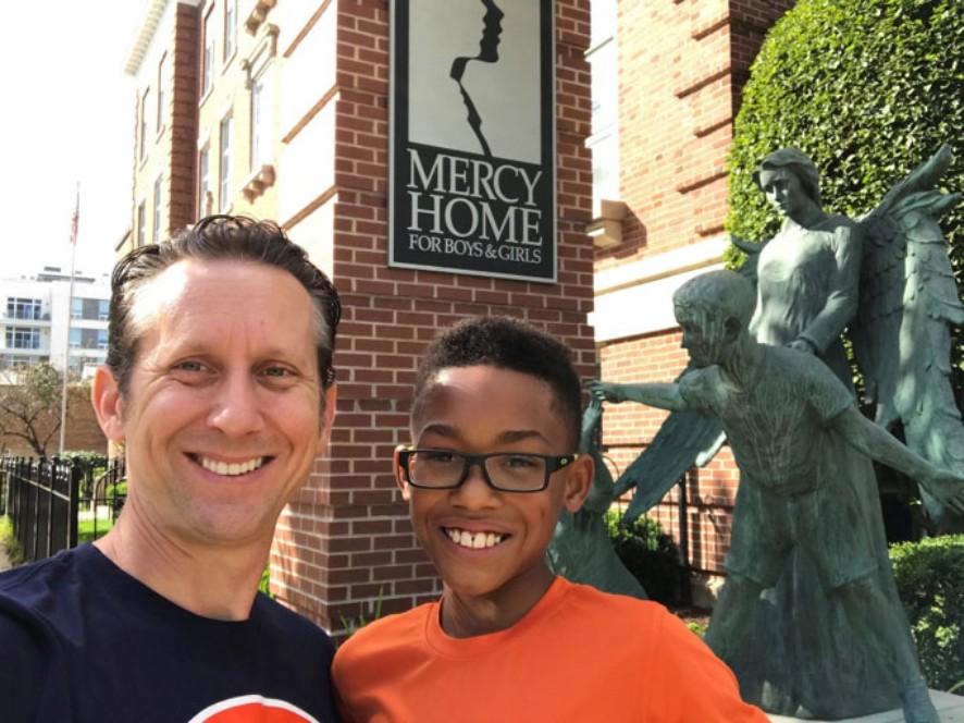 """Scott e seu filho adotivo Demetrius sorriem em frente ao orfanato """"Mercy Home"""" - exatamente onde o avô de Scott um dia encontrou um novo lar."""