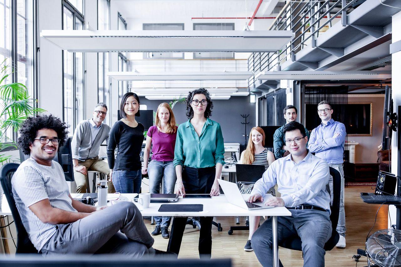 Neun Menschen sitzen oder stehen zusammen in einem Raum