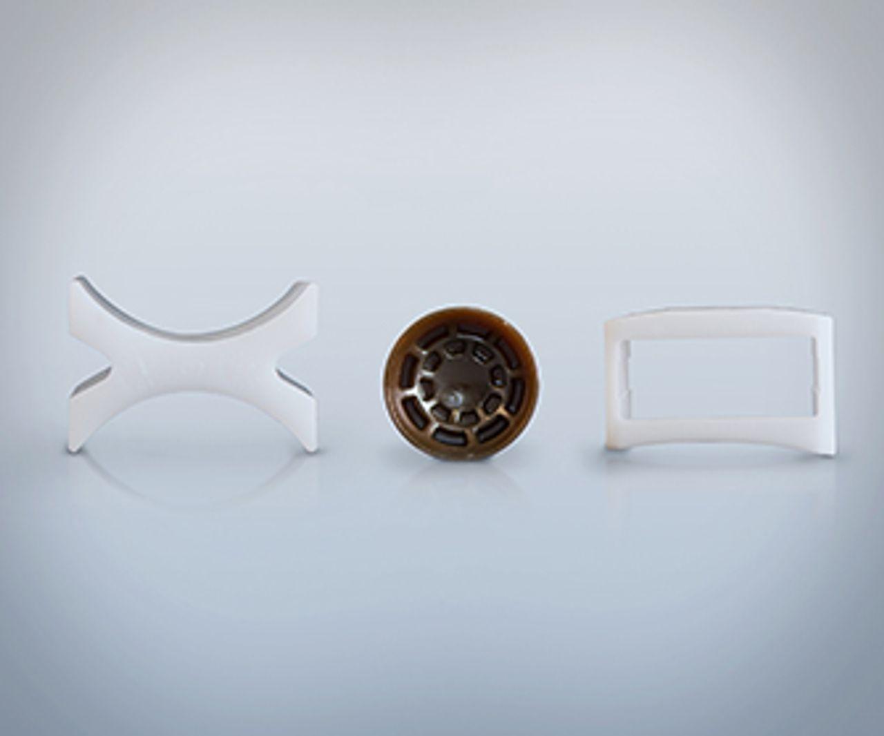Drei Kunststoffteile, X-Form, rund und rechteckig auf grauem Hintergrund