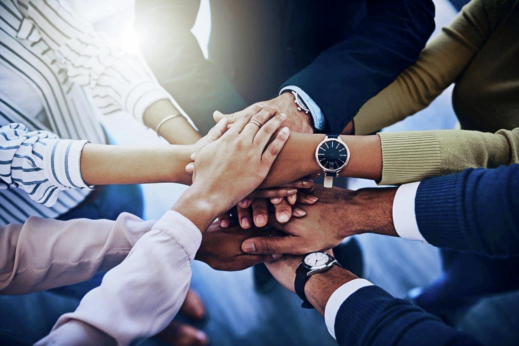 Sechs Personen legen ihre Hände übereinander