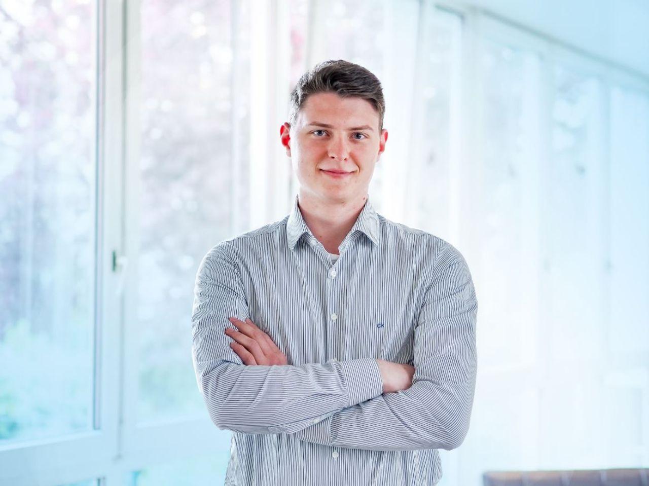 Ben Scheifers, mit verschränkten Armen vor einer Fensterfront stehend