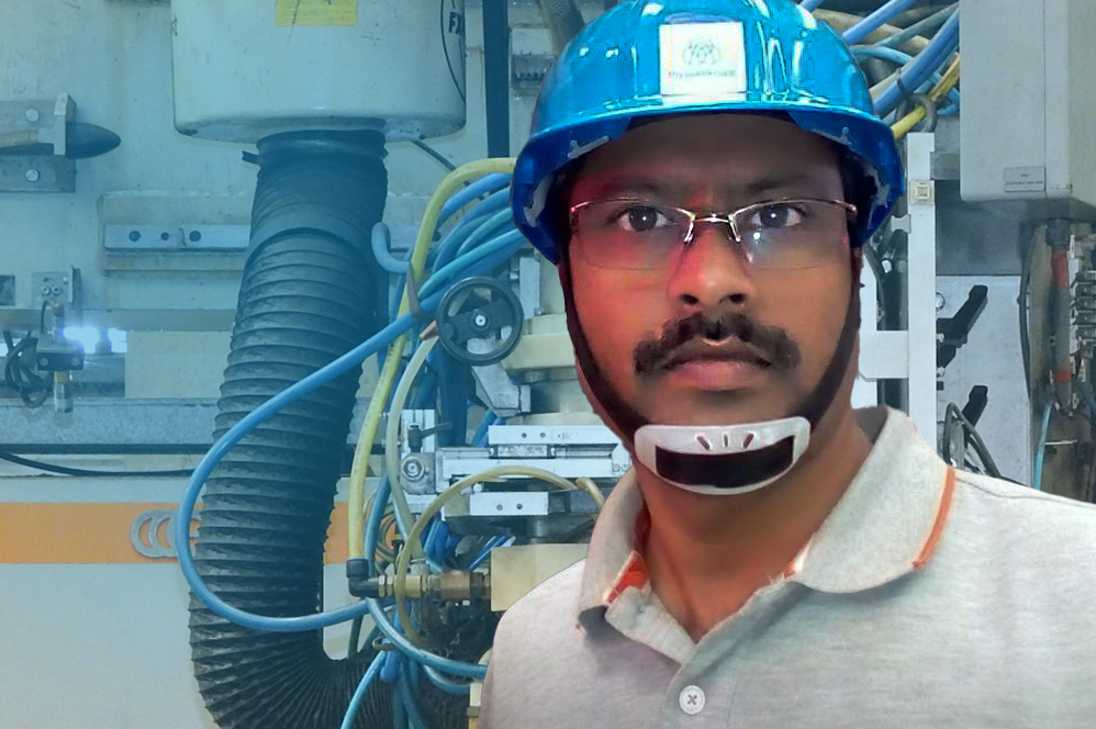 Santosh Rahane, wearing work uniform and standing in front of a machine