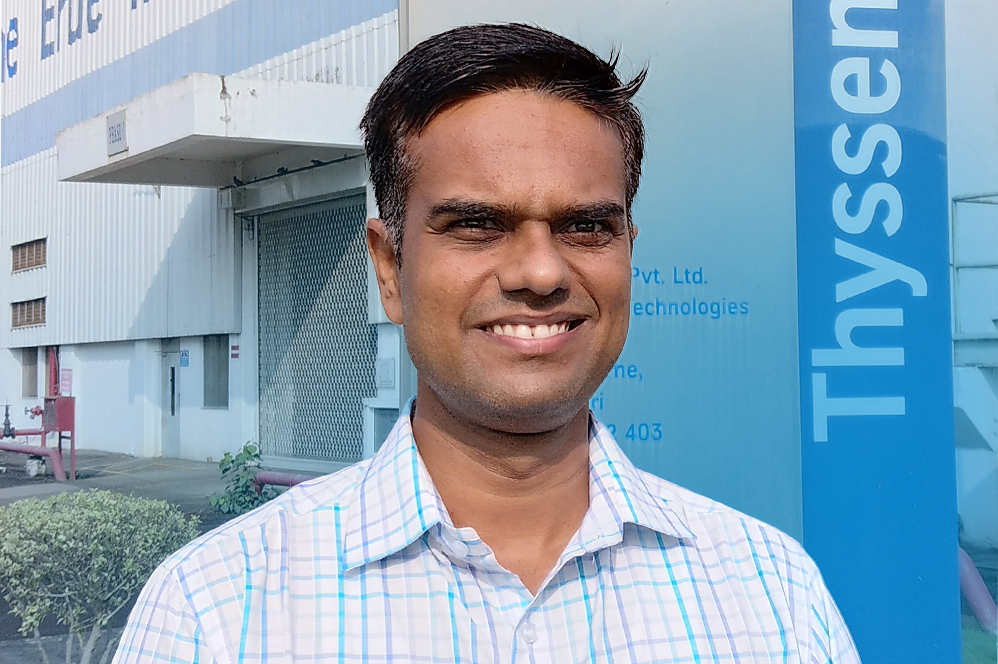 Ajay Aralkar, smiling, standing in front of a thyssenkrupp building