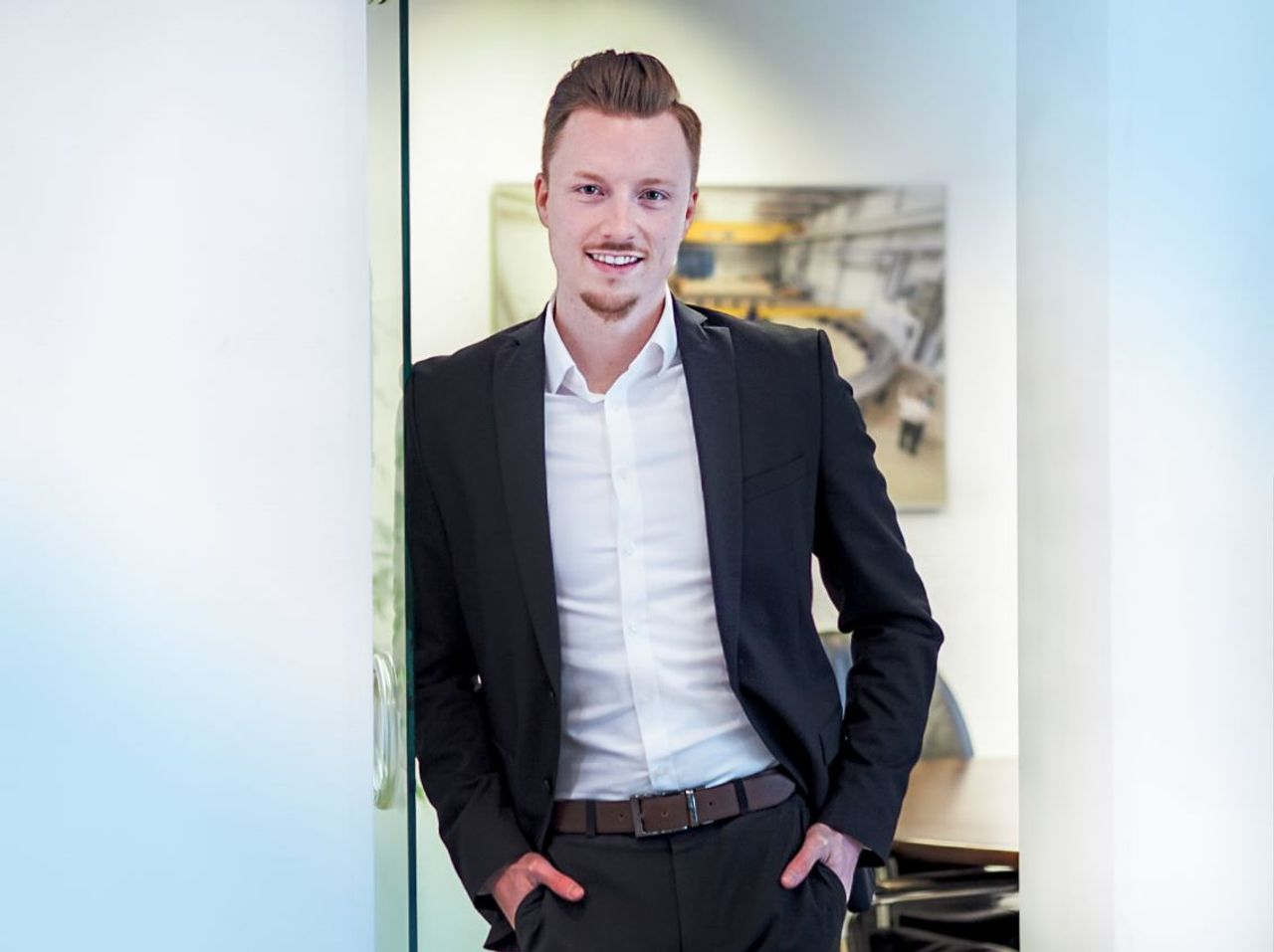 Niklas Barrenpohl smiling, standing in a door, leaning against a wall in front of an office