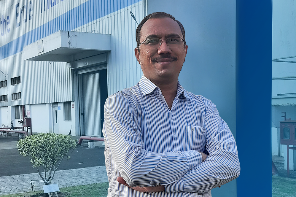 Nilesh Patil - Operational Buyer, amrs corssed, standing in front of a building