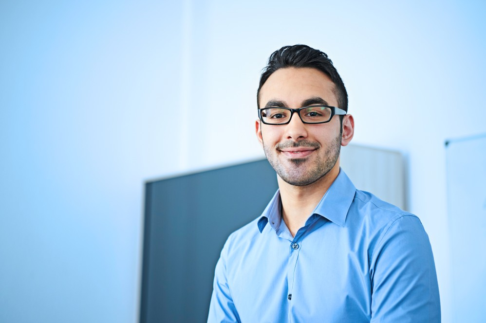 Tarik Calti, wearing glasses, wearing a blue shirt, standing in front of a wall