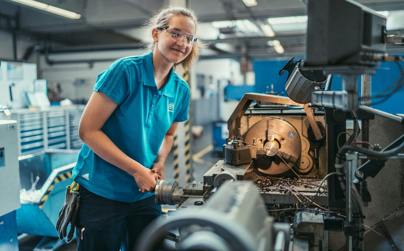 Janina Jäger, machining mechanic apprentice, smiling while working at a machine