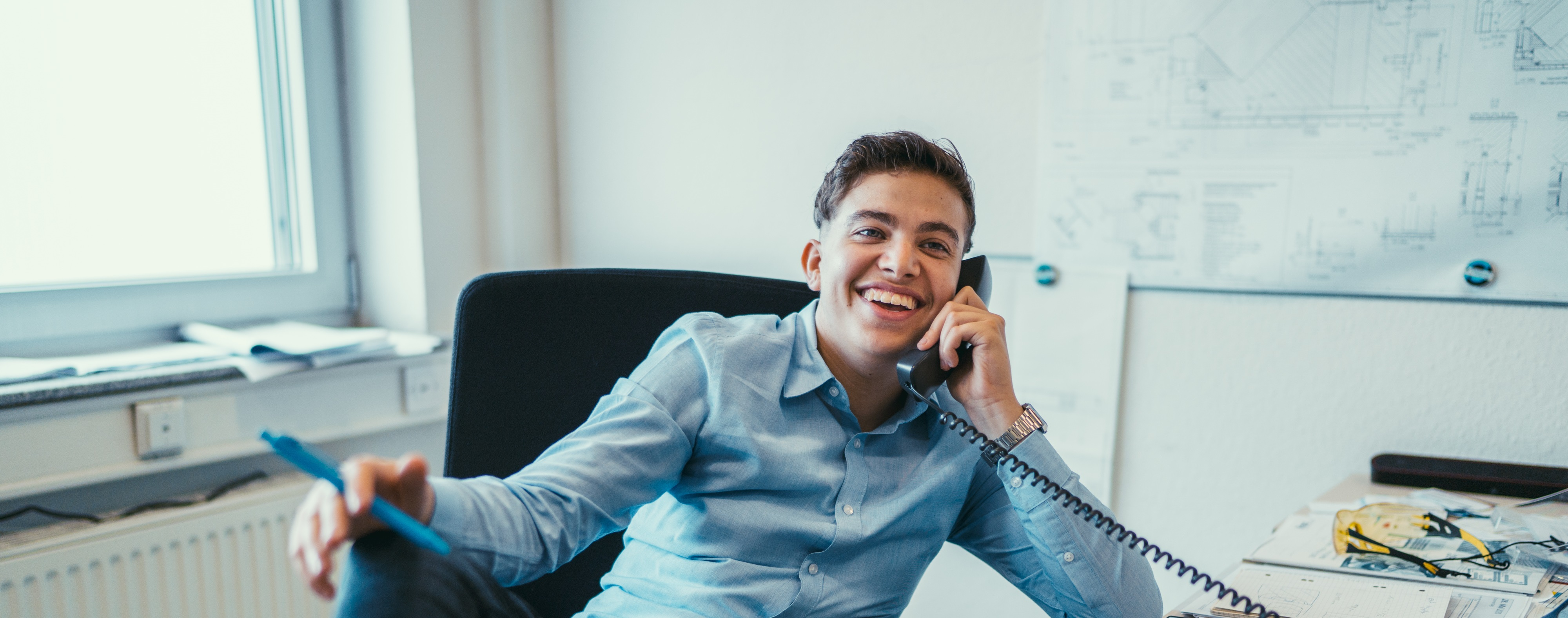 Industrial clerk apprentice sitting at a desk, smiling while talking on the phone