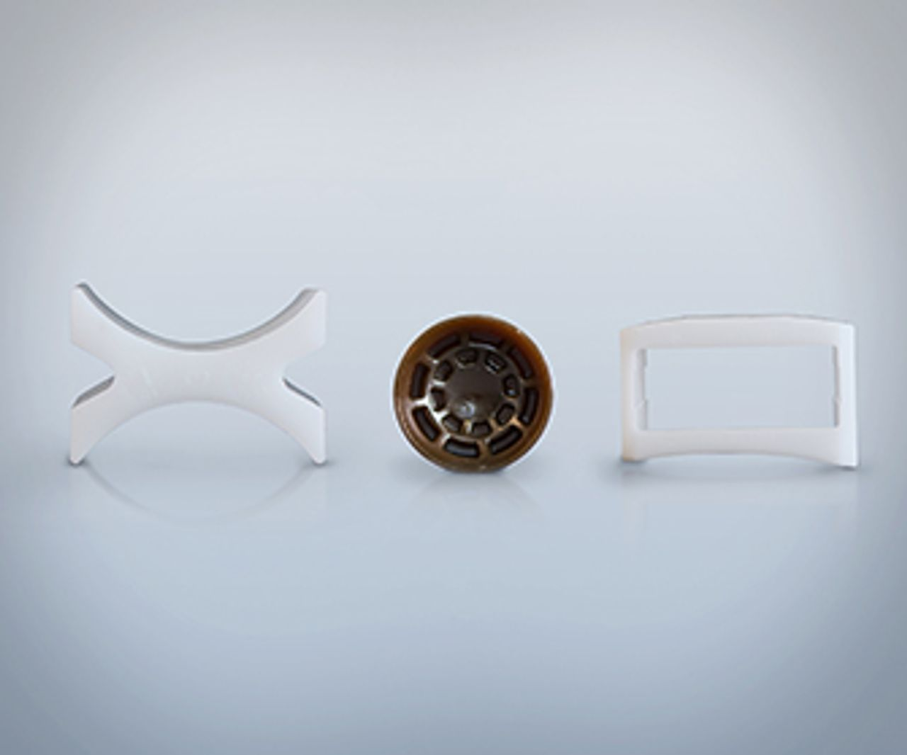 Tres piezas de plástico, en forma de X, redondas y rectangulares sobre un fondo gris