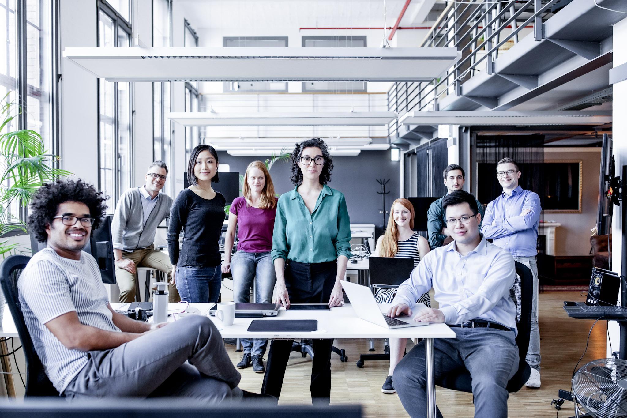 Neuf personnes s'assoient ou se tiennent ensemble dans une même pièce