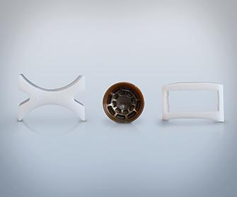Trois pièces en plastique, en forme de X, rondes et rectangulaires sur fond gris