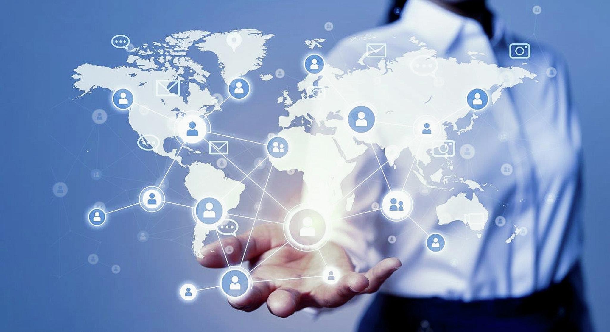 Una persona indossa una maglietta e tende la mano. Una mappa del mondo con una rete esce dalla mano