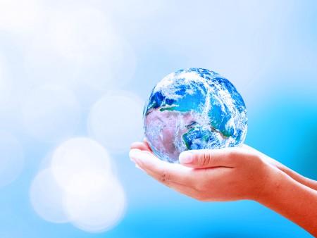 Due mani tengono un globo di vetro in una mano su uno sfondo blu