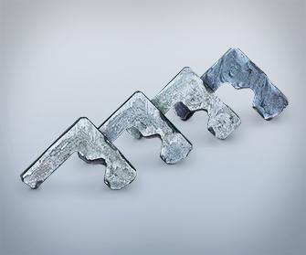 Quattro profili in acciaio su fondo grigio
